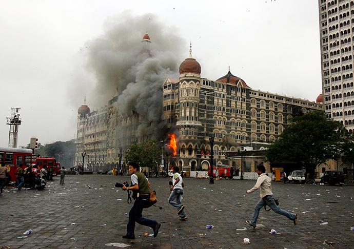 ARCHIVE PHOTO: Photographers run past burning Taj Mahal Hotel during a gun battle in Mumbai November 29, 2008 (Reuters / Arko Datta)
