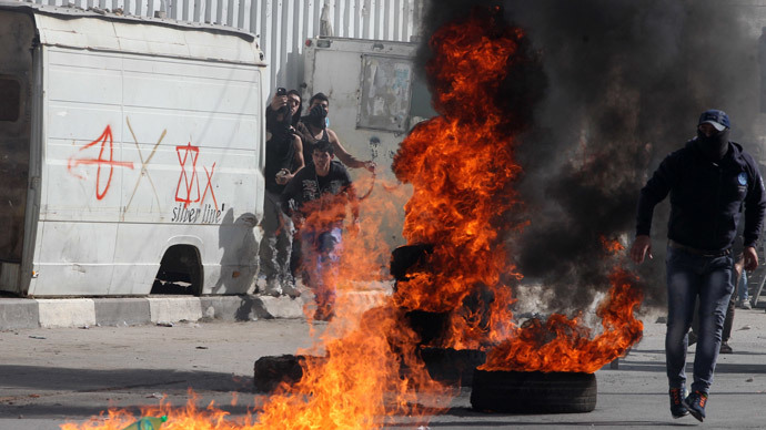 Palestinian protestors stand near burning tyres during clashes with Israeli security forces in the West Bank city of Hebron following a demonstration in support of Palestinians entering the Al-Aqsa mosque compound in Jerusalem for Friday prayers on November 14, 2014.(AFP Photo / Hazem Bader)