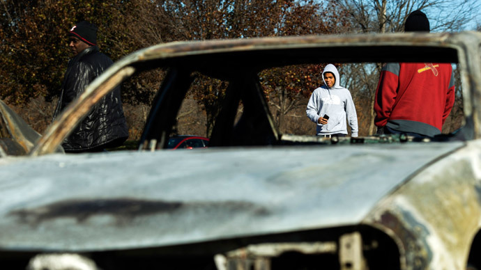 People walk towards a car lot where several cars had been burned and damaged following a night of rioting in Ferguson, Missouri November 25, 2014.(Reuters / Lucas Jackson)