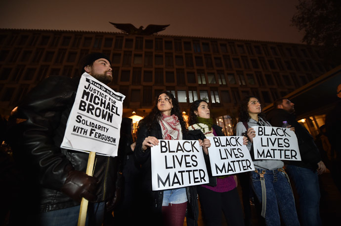 Demonstrators stand and chant with placards during a protest outside the US embassy in London on November 26, 2014 over the US court decision not to charge the policeman who killed unarmed black teenager Michael Brown in the town of Ferguson. (AFP Photo/Leon Neal)