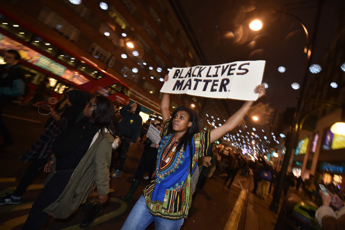 Demonstrators hold up placards and march down Oxford Street in central London on November 26, 2014 during a protest over the US court decision not to charge the policeman who killed unarmed black teenager Michael Brown in the town of Ferguson. (AFP Photo/Leon Neal)
