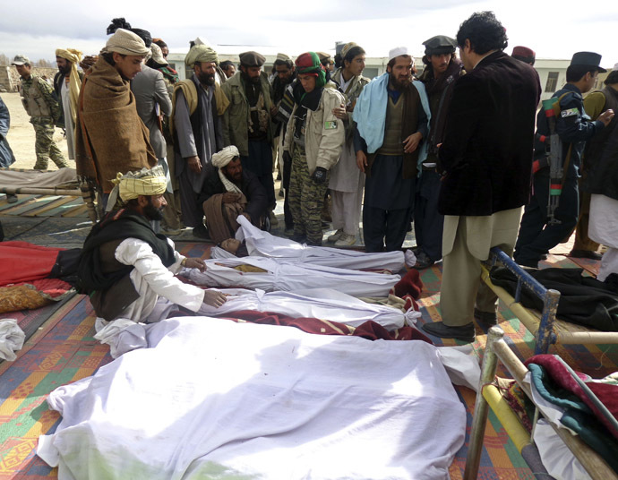 Afghan men gather around the bodies of victims of Sunday's suicide attack at a volleyball match in Yahya Khail district, Paktika province, November 24, 2014. (Reuters/Stringer)