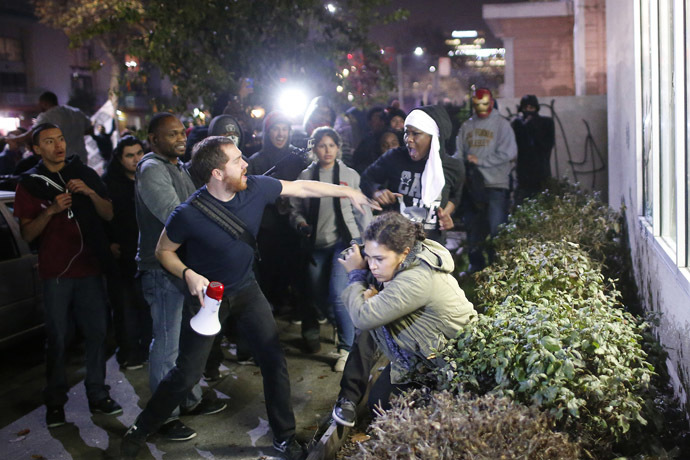 A man attempts to stop a protester from confronting another protester (bottom), who fell into the bushes while trying to protect a convenience store, during a demonstration following the grand jury decision on Monday in the Ferguson, Missouri shooting of Michael Brown, in Oakland, California, November 26, 2014. (Reuters/Stephen Lam)