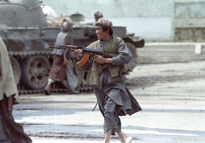 A Dostum mujahideen fighter runs as he fires his AK-47 machine gun against advancing Hezb-i-Islami rebels at the Bala Hishar palace in Kabul on April 26, 1992. (Reuters/Richard Ellis)