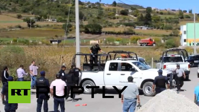 Mexican police inspecting the scene where 11 dead bodies were found on the side of a road in Chilapa on November 27, 2014. (A still from Ruptly video)