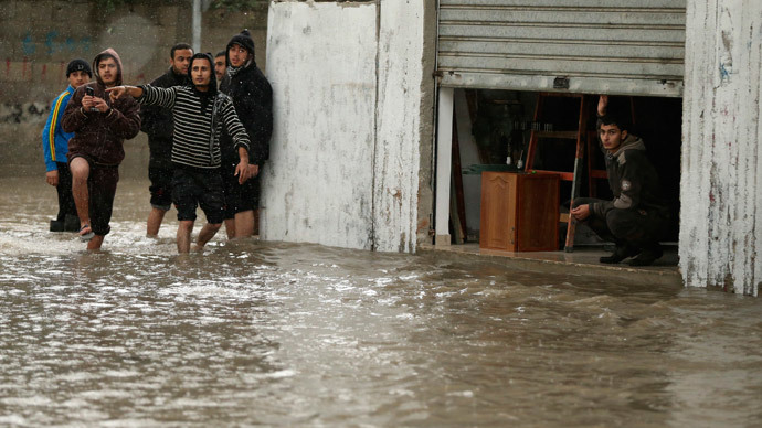 A man looks out of his shop as Palestinians walk through a flooded road following heavy rain in Gaza City November 27, 2014.(Reuters / Mohammed Salem)