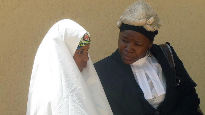 14-year old Wasila Tasiu speaks with an unidentified defence counsel outside the courtroom during a 30-minute break during her first day of trial at Kano state High Court in the village of Gezawa outside Kano on October 30, 2014. (AFP Photo/Aminu Abubakar)