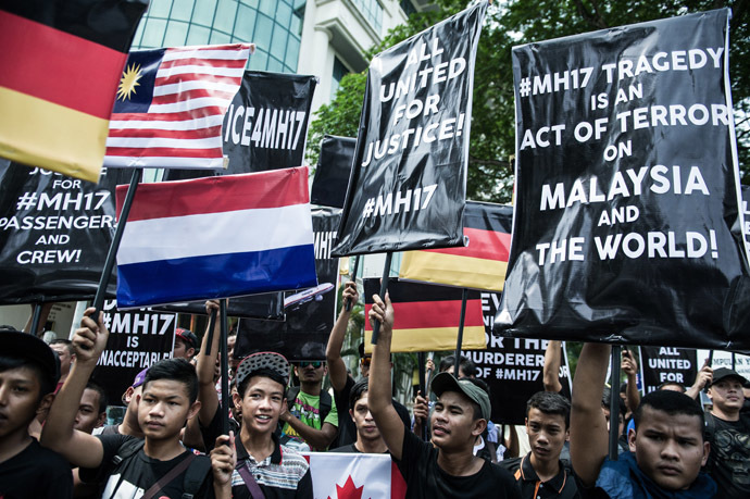 Youths hold placards and Malaysian flags during a Malaysia Airlines flight MH17 solidarity gathering outside the Parliament house in Kuala Lumpur July 23, 2014. (AFP Photo)