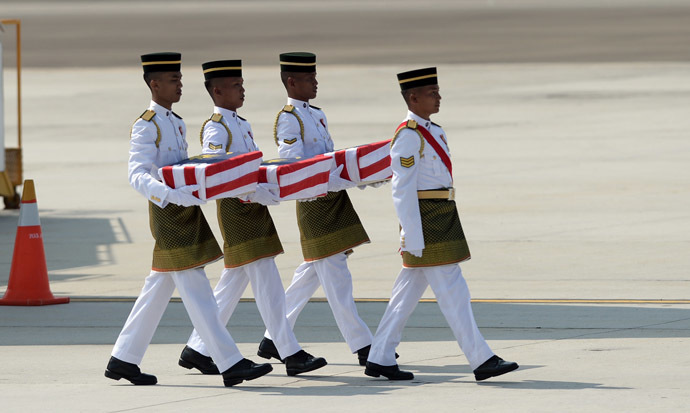 Soldiers carry coffins with the remains of Malaysian victims from the Malaysia Airlines flight MH17 that crashed in Ukraine during a ceremony at the Bunga Raya complex at Kuala Lumpur International Airport in Sepang on August 22, 2014. (AFP Photo)