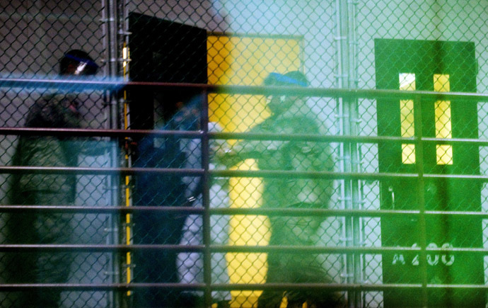 """This image reviewed by the US military shot through a one way mirror shows guards moving a detainee from his cell in Cell Block A of the """"Camp Six"""" detention facility of the Joint Detention Group at the US Naval Station in Guantanamo Bay (AFP Photo)"""