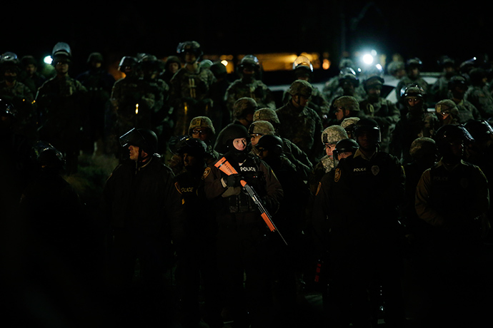 A demonstrator protesting the shooting death of Michael Brown shines a spot light on a group of police officers and National Guard troops outside of the Ferguson Police Station November 28, 2014 in Ferguson, Missouri (AFP Photo / Joshua Lott)