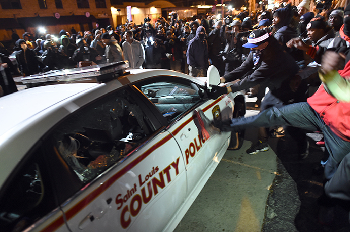 Protesters attack a police car during clashes following the grand jury decision in the death 18-year-old Michael Brown in Ferguson, Missouri, on November 24, 2014 (AFP Photo / Jewel Samad)