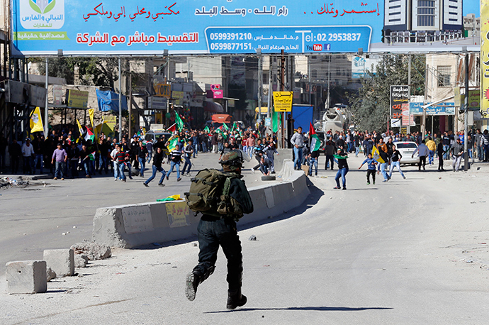 An Israeli border policeman runs during clashes with Palestinian stone throwers following a protest against what organizers say are recent visits by Jewish activists to al-Aqsa mosque, at Qalandia checkpoint near the West Bank city of Ramallah November 7, 2014 (Reuters / Ammar Awad)