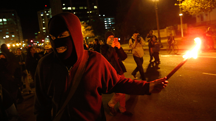 A masked protester holds a flare during a demonstration, following the grand jury decision in the Ferguson, Missouri shooting of Michael Brown, in Oakland, California November 24, 2014 (Reuters / Stephen Lam)