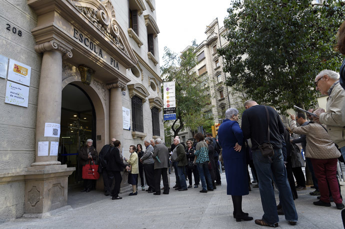 People wait on November 9, 2014 outside a school in Barcelona to vote in a symbolic ballot on whether to break away as an independent state, defying fierce challenges by the Spanish government. (AFP Photo/Lluis Gene)