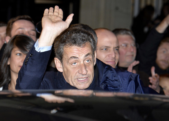 Former French President Nicolas Sarkozy, elected at the helm of the French right-wing main opposition party UMP, cheers his fans as he leaves on November 29, 2014 the UMP's headquarters in Paris. (AFP Photo/Miguel Medina)