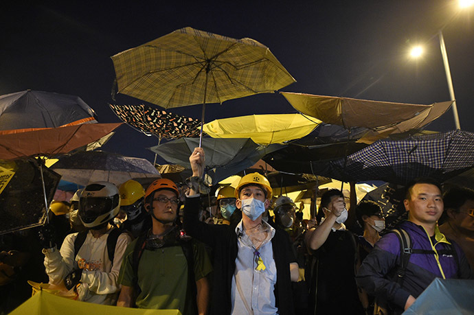 Demonstrators hold umbrellas, a symbol of the pro-democracy protests, amid a clash with police during the protest near the government headquarters in Hong Kong on November 30, 2014. (AFP Photo/Philippe Lopez)