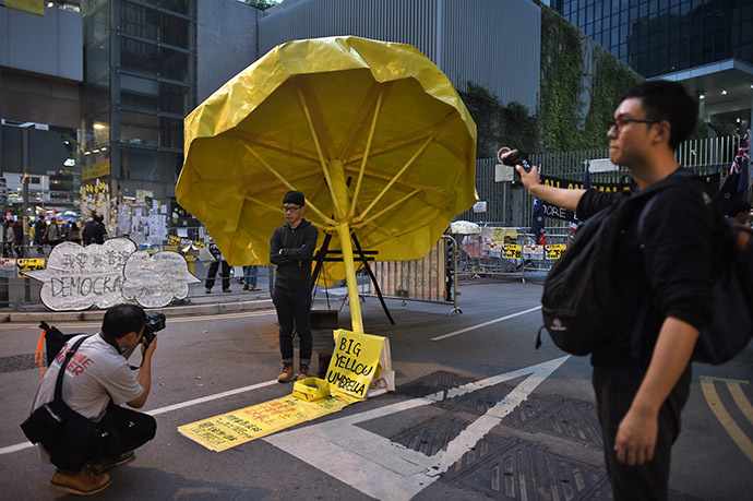 A man poses for a photograph under a yellow umbrella, a symbol of the pro-democracy protests, in the Admiralty district of Hong Kong on November 30, 2014. (AFP Photo/Philippe Lopez)