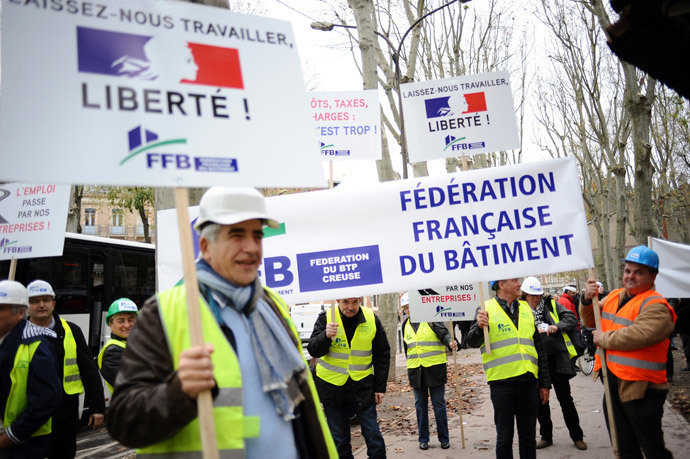 "Members of the ""Federation Francaise du Batiment"" hold signs (L) reading ""Let us work, freedom!"" as French bosses protest on December 1, 2014 in Toulouse against 30 years of government economic policies that have, according to them, stunted economic growth. (AFP Photo / Remy Gabalda)"