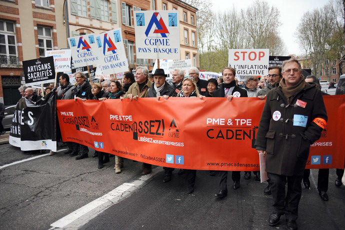 "French business owners hold signs of the ""Confederation Generale des Petites et Moyennes Entreprises"" (CGPME) as they protest on December 1, 2014 in Toulouse against hefty taxes, charges and stifling regulations they say are driving their firms into the ground. (AFP Photo / Remy Gabalda)"