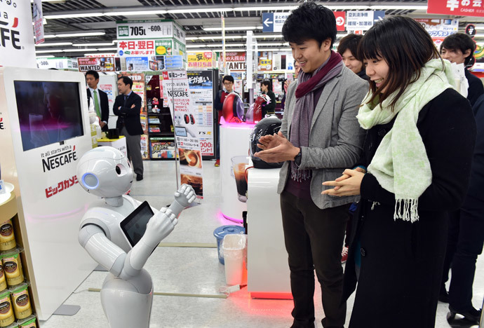 Japanese telecom giant Softbank's humanoid robot Pepper (L) attends to customers to introduce Nestle's coffee machines at an electric shop in Tokyo on December 1, 2014. (AFP Photo / Yoshikazu Tsuno)