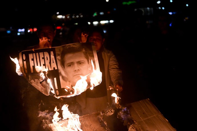 Demonstrators burn a banner bearing the image of Mexican President Enrique Pena Nieto along Reforma Avenue during a protest demanding justice in the case of the 43 missing students from Ayotzinapa, on December 1, 2014 in Mexico City. (AFP Photo / Yuri Cortez)