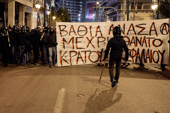 "Anarchists carry a banner reading ""Deep breath until the death of the state and the capital"" in Athens on December 2, 2014 during a massive march in solidarity with a 22-years old anarchist hunger striker, Nikos Romanos (AFP Photo / Louisa Gouliamaki)"