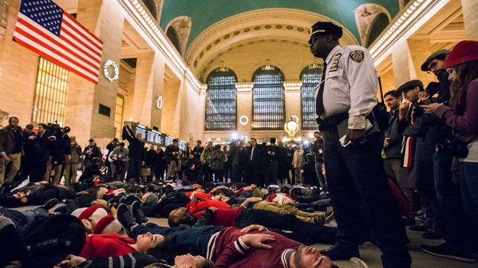 A police officer stands over activists, demanding justice for the death of Eric Garner, as they stage a 'die-in' during rush hour at Grand Central Terminal in the Manhattan borough of New York on December 3, 2014.(Reuters / Adrees Latif)