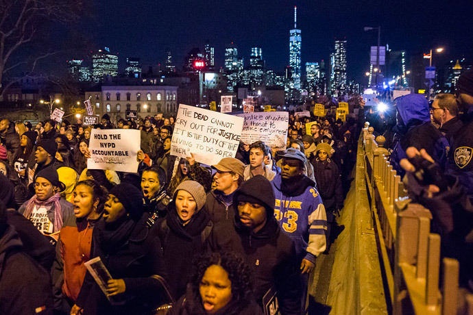 The Lower Manhattan skyline, including One World Trade Center, is seen in the background as protesters, demanding justice for Eric Garner, enter Brooklyn off the Brooklyn Bridge in New York December 4, 2014. (Reuters / Elizabeth Shafiroff)