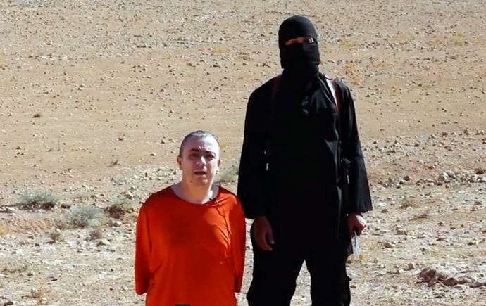 "An image grab taken from a video released by the Islamic State (IS) via its ""Al-Furqan » media arm on October 3, 2014 purportedly shows a masked militant (R) before the execution of British hostage Alan Henning dressed in orange and on his knees in a desert landscape. (AFP Photo / HO)"