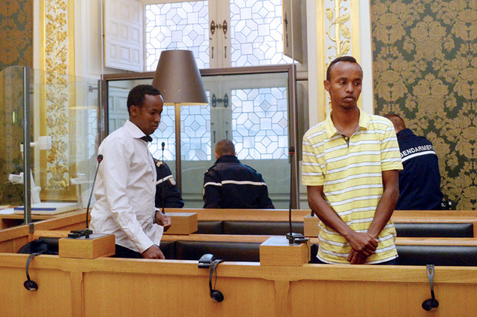 Two of the three Somali pirates arrested by French soldiers in 2009 Mahmoud Abdi Mohammed (L) and Abdelkader Osmane Ali wait in the accused box, on October 14, 2013 at Rennes' courthouse, prior to the opening hearing of their trial for hijacking a yacht in 2009. (AFP Photo / Damien Meyer)