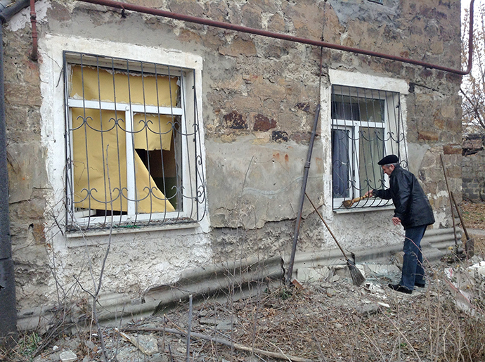 A residents of Azotny district clears the area around his house following shelling which killed a 12-year-old boy and a 55-year-old woman, Donetsk, Ukraine (RIA Novosti)