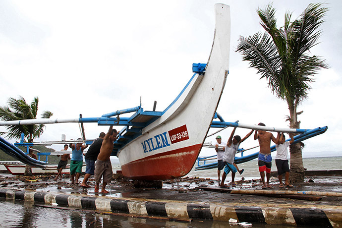 Fishermen carry thier outrigger to higher ground in Legazpi City, south of Manila on December 5, 2014, ahead of the landfall of Typhoon Hagupit. (AFP Photo/Charism Sayat)
