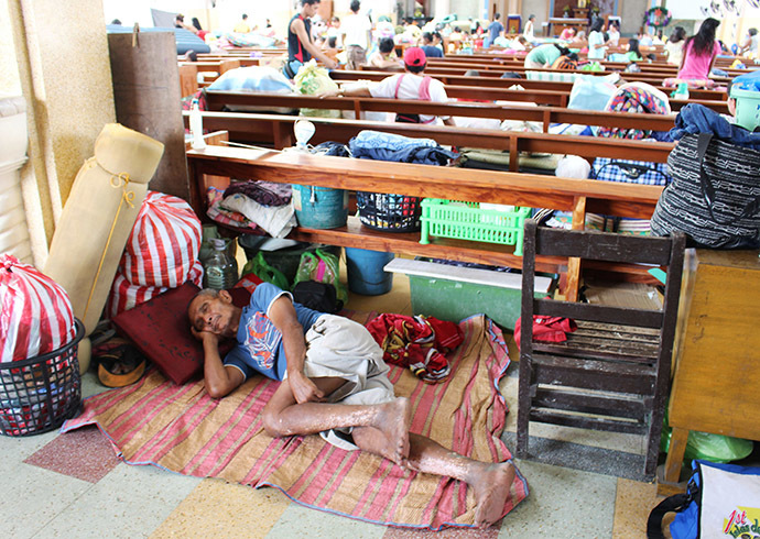 A man rests inside a church after residents evacuated their homes due to super-typhoon Hagupit in Tacloban city, central Philippines December 5, 2014.(Reuters/Rowel Montes)