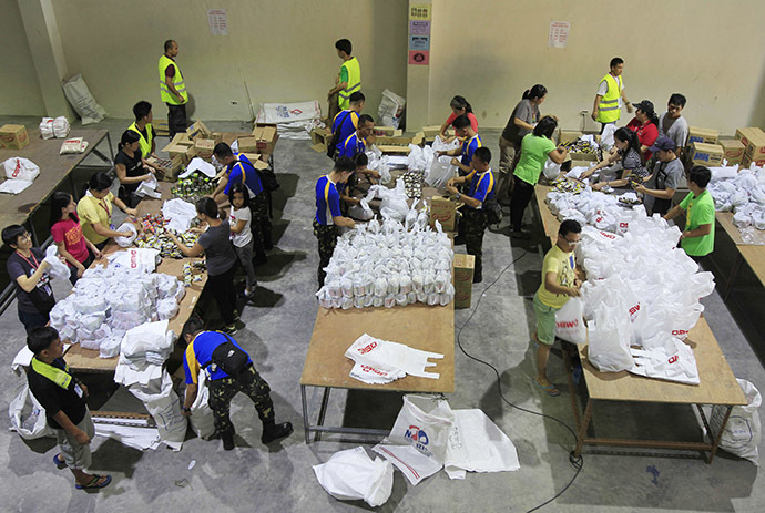 Soldiers and volunteers prepare relief goods, to be delivered before Typhoon Hagupit makes landfall, inside a Department of Social Welfare and Development (DSWD) warehouse in Manila, December 6, 2014. (Reuters/Romeo Ranoco)