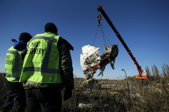 Investigators watch as a piece of wreckage from the Malaysia Airlines flight MH17 is transported at the site of the plane crash near the village of Hrabove (Grabovo) in Donetsk region, eastern Ukraine November 20, 2014. (Reuters/Antonio Bronic)