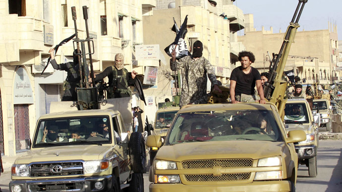 Militant Islamist fighters in military vehicles parade along the streets of Syria's northern Raqqa province, June 30, 2014. (Reuters)