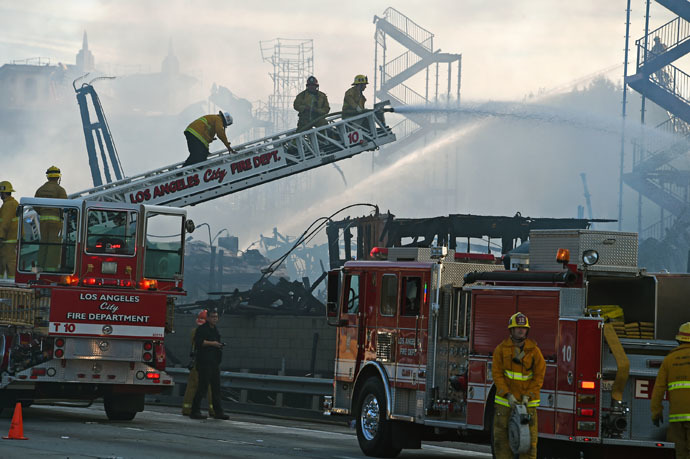 Firefighters douse the remains of a fire that destroyed an apartment complex that was under construction, in downtown Los Angeles, California, December 8, 2014. (AFP Photo/Robyn Beck)