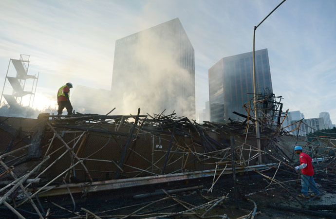 Workers survey damage after a huge fire in downtown Los Angeles, California, December 8, 2014. (AFP Photo/Robyn Beck)