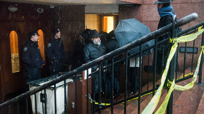 Police keep guard as men walk past police tape outside of the world headquarters of the Chabad-Lubavitch movement, the scene of a stabbing at the Brooklyn synagogue in New York City December 9, 2014.(Reuters / Stephanie Keith)
