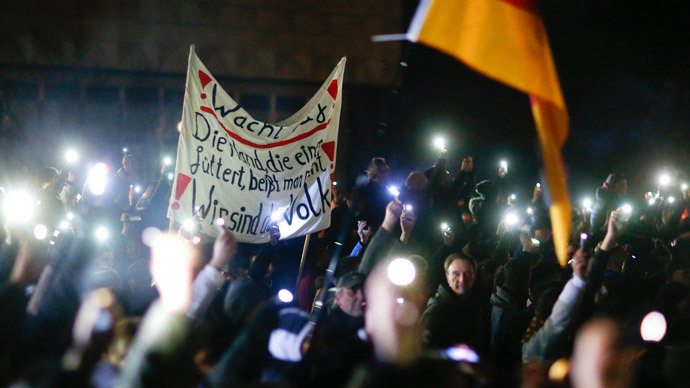 "Participants hold up their mobile phones and wave a German national flag during a demonstration called by anti-immigration group PEGIDA, a German abbreviation for ""Patriotic Europeans against the Islamization of the West"", in Dresden December 8, 2014.(Reuters / Hannibal Hanschke)"
