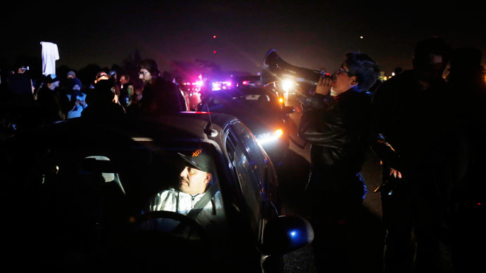 A stranded motorist sits in his car as protesters block traffic on Highway 80 during a march against the New York City grand jury decision to not indict in the death of Eric Garner in Berkeley, California December 8, 2014. (Reuters / Stephen Lam)