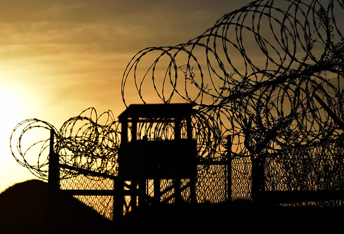 "This photo made during an escorted visit and reviewed by the US military, shows the razor wire-topped fence and a watch tower at the abandoned ""Camp X-Ray"" detention facility at the US Naval Station in Guantanamo Bay, Cuba. (AFP Photo/Mladen Antonov)"