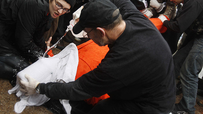 Protestors perform a simulation of the waterboarding torture technique on a man dressed as a prisoner during a protest. (Reuters/Jim Young)