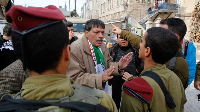 Palestinian Ziad Abu Ein (C), Head of the Anti-wall and Settlement Commission, argues with Israeli soldiers as they prevent him from crossing to Al-Shuhada Street in the West Bank city of Hebron November 29, 2014.(Reuters / Mussa Qawasma)