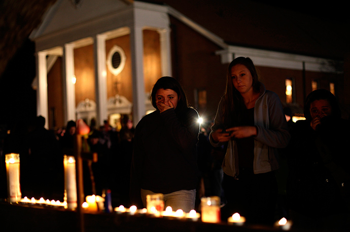 ARCHIVE PHOTO: A woman covers her mouth as others look on stand near candles outside Saint Rose of Lima Roman Catholic Church near Sandy Hook Elementary School, where a gunman opened fire on school children and staff in Newtown, Connecticut December 14, 2012 (Reuters / Joshua Lott)