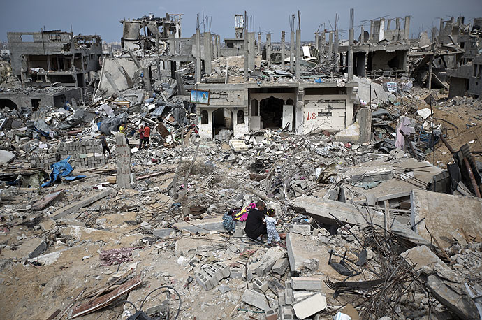 Palestinians walk amidst destroyed buildings in al-Tufah, east of Gaza City on October 11, 2014 (AFP Photo/Mahmud Hamas)