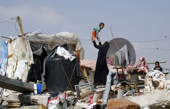 A Palestinian woman plays with her child on the rubble of their family's home which was destroyed during the 50-day Gaza war between Israel and Hamas-led militants in the Gaza Strip, on November 12, 2014, in Khan Yunis' Khuzaa neighbourhood in the southern Gaza Strip near the Israeli border. (AFP Photo)
