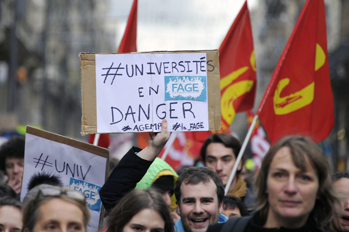 "A man holds a placard reading ""Universities in danger"" as protesters march on December 11, 2014 in Toulouse, southern France, during a demonstration called by unions and the collective ""Sciences en Marche"", to denounce budget cuts in higher education and research. (AFP Photo/Pascal Pavani)"