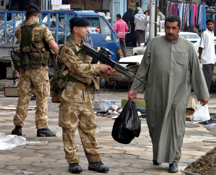 An Iraqi man passes British soldiers patrolling the streets in the southern city of Basra, some 600 km of Baghdad December 6, 2003. (Reuters/Atef Hassan)